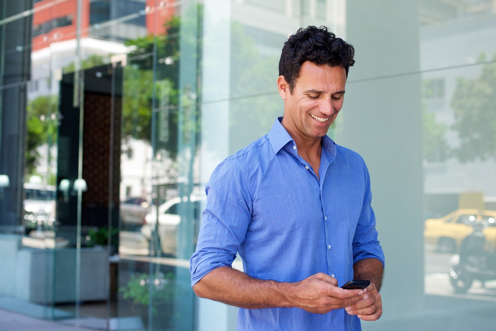 Portrait of a business man walking with mobile phone